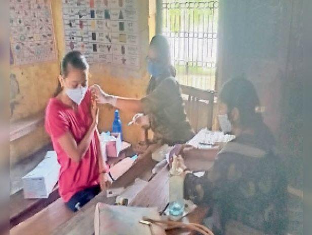 मिडिल स्कूल रेलवे कॉलोनी में वैक्सीन लेती युवती। - Dainik Bhaskar