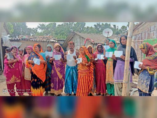 भकुआ के वार्ड-12 में अपना कार्ड दिखाते ग्रामीण। - Dainik Bhaskar