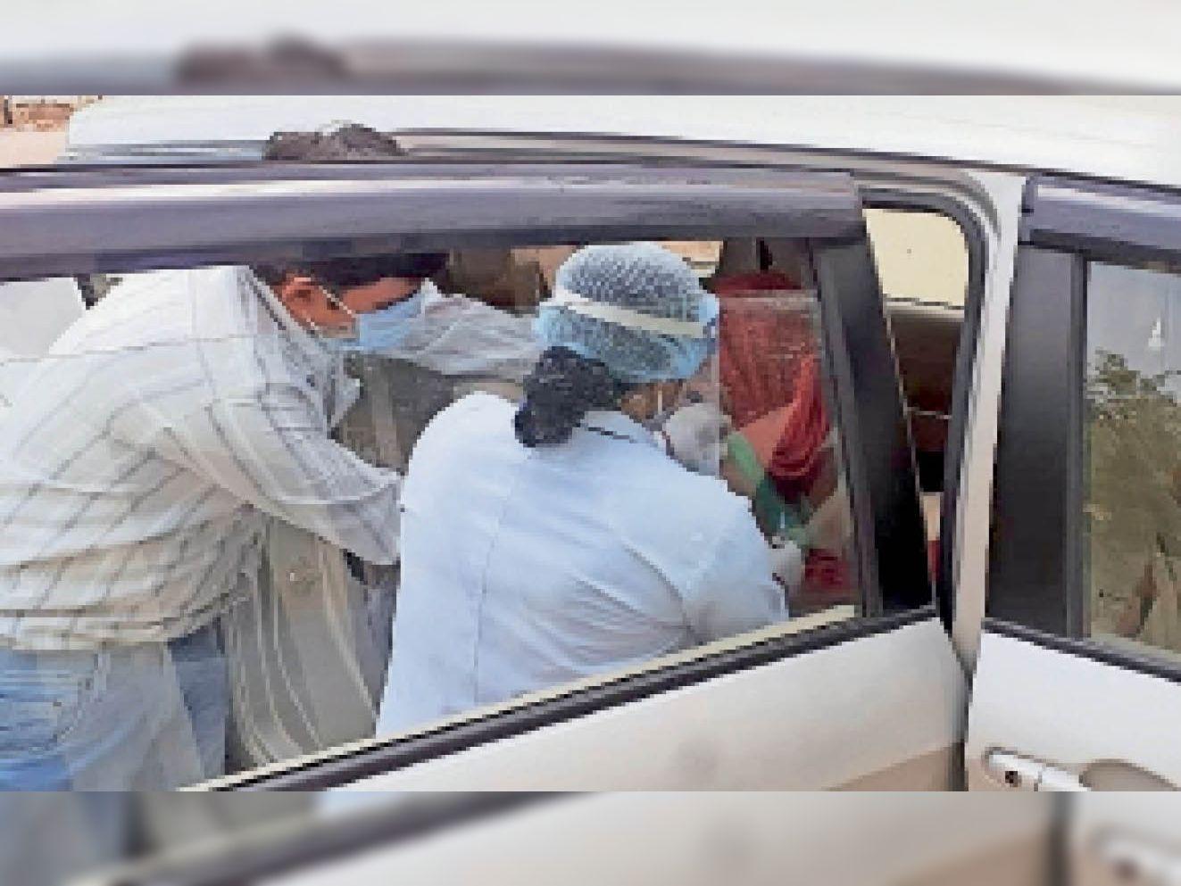 छतरपुर। कार में बैठे 18 साल से अधिक आयु के व्यक्ति को वैक्सीनेशन लगाती स्वास्थ्य विभाग की टीम। - Dainik Bhaskar