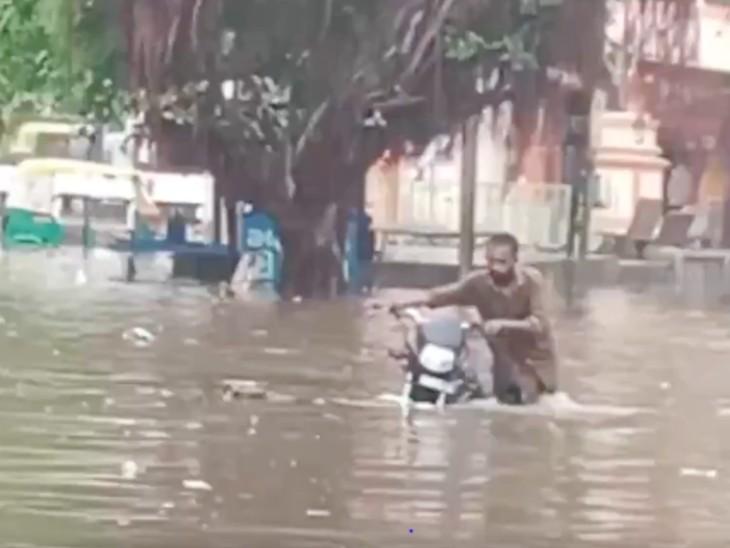 गुजरात के आणंद में तेज बारिश के बाद पानी भरा गया। इसी दौरान एक बाइक सवार अपनी गाड़ी निकालता हुआ।