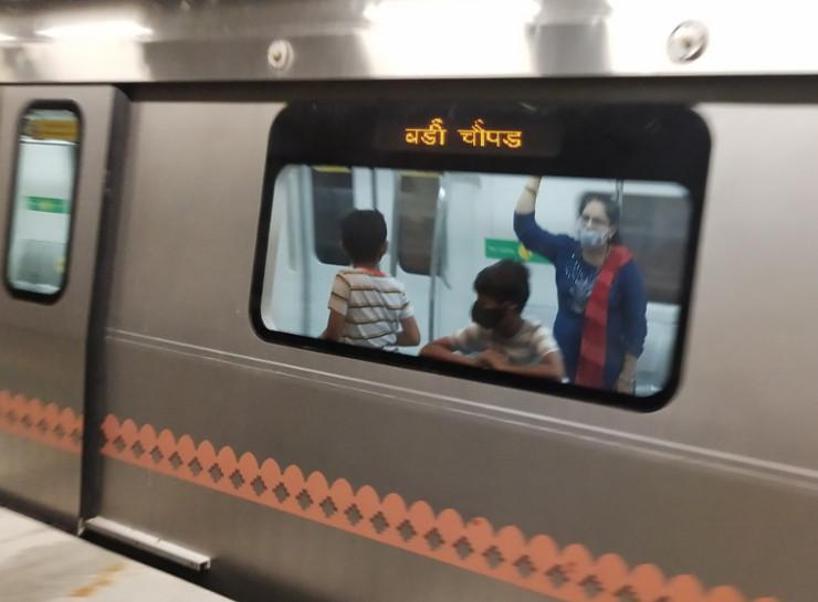 मम्मी के साथ मेट्रो में आनंद लेते हुए बच्चे