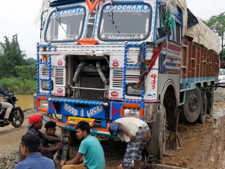 ट्रक को गड्ढे से बाहर निकालने के प्रयास में जुटे लोग।
