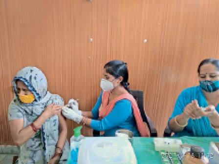 सिविल अस्पताल में एक महिला को वैक्सीन लगाते हुए स्वास्थ्य कर्मी। - Dainik Bhaskar