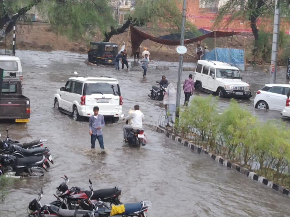 सड़कों पर बहता पानी, दुपहिया वाहनों को खींचते वाहन चालक