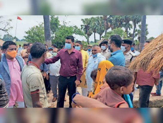 गांव में ग्रामीणों को टीका के फायदे बताते जिलाधिकारी व अन्य। - Dainik Bhaskar