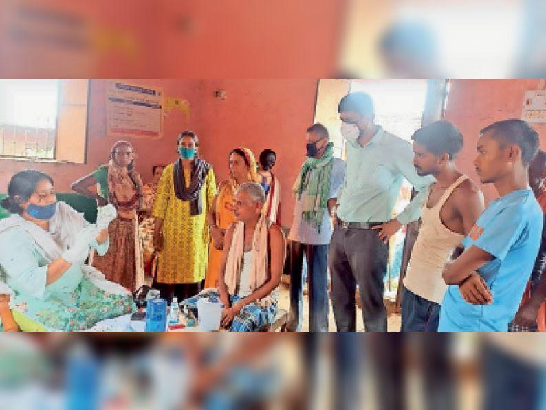 नूरसराय महादलित टोला के आंगनबाड़ी केंद्र पर हो रहे वैक्सीनेशन का जायजा लेते बीडीओ सह सीओ। - Dainik Bhaskar