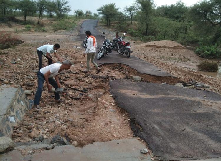 बरसात से टूटी देसूरी क्षेत्र के उन्दरथल-बडौद मार्ग पर बनी डामर सड़क मार्ग को दुरुस्त करते ग्रामीण।