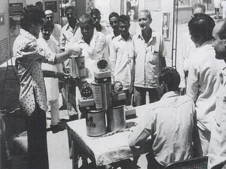 एक नसबंदी कैंप के बाहर नसबंदी कराने आए पुरुषों को घी का डिब्बा और घड़ी देते हुए कर्मचारी।