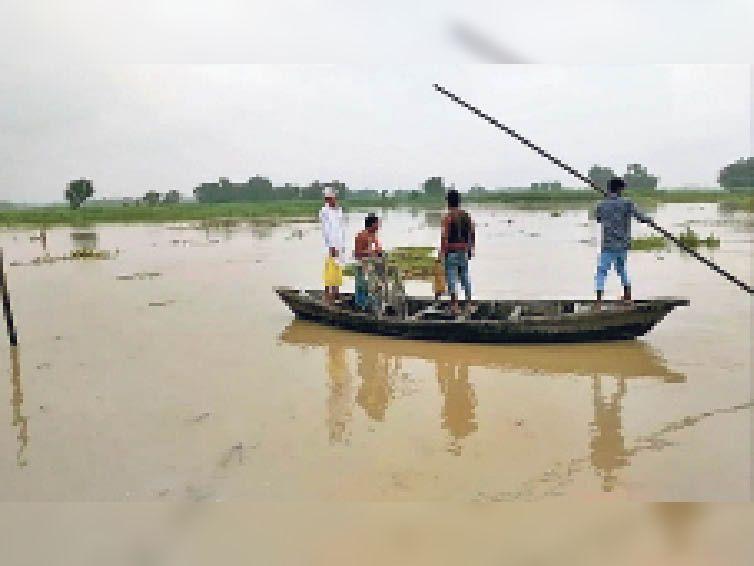 कुमारखंड के टिकुलिया स्थित संगम घाट पर नाव से नदी पार करते लोग। - Dainik Bhaskar