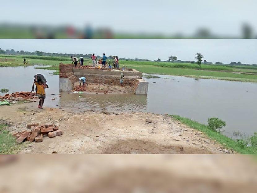 सड़क में चल रहा पुल निर्माण कार्य व बगल में जमा पानी। - Dainik Bhaskar