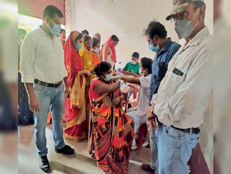 महिला को वैक्सीन देती स्वास्थ्यकर्मी। - Dainik Bhaskar