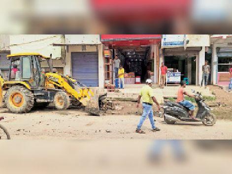 मुख्य बाजार में सफाई का कार्य कराते अधिकारी। - Dainik Bhaskar