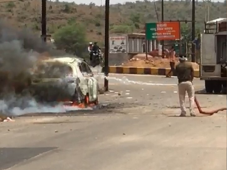 जलती कार को बुझाने का प्रयास करते दमकलकर्मी, जब तक आग बुझाई तो कार पूरी जल चुकी थी