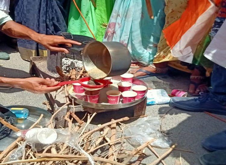 चाय बनने के बाद उन्हें कप में भरते हुए एक कार्यकर्ता।