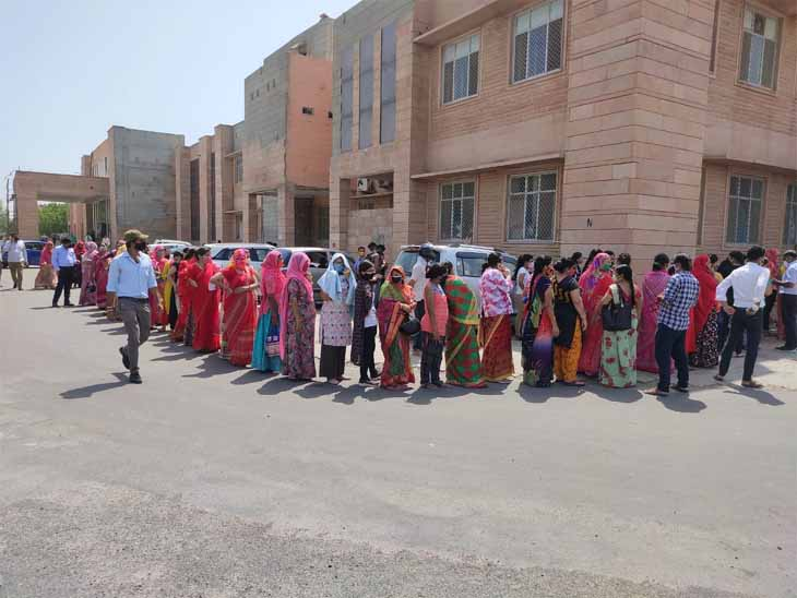 वैक्सीन लगवाने के लिए धूप के बावजूद कतार में खड़ी महिलाएं।