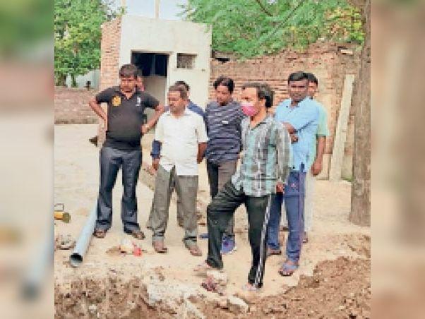 सिटी के कबीर नगर में पानी की पाइपलाइन के बारे में जानकारी देते लाेग। - Dainik Bhaskar