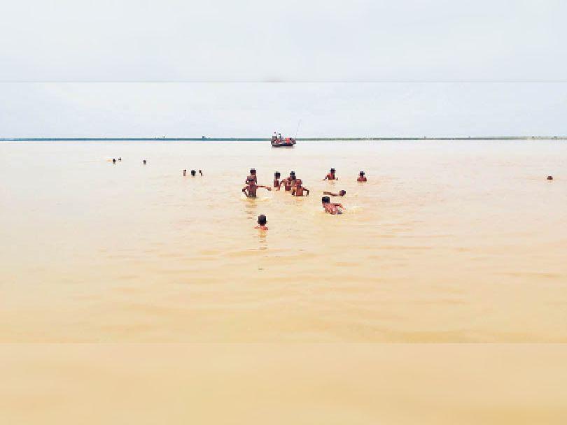 बुधवार को टिकारामपुर दियारा क्षेत्र में फैला बाढ़ का पानी, मुख्य धार में नाव जबकि खेतों में फैले पानी में नहाते बच्चे। - Dainik Bhaskar