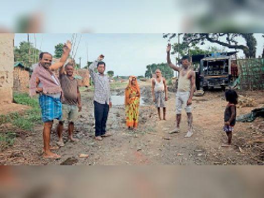 सड़क पर बने गड्ढे की मरम्मती की मांग करते ग्रामीण। - Dainik Bhaskar