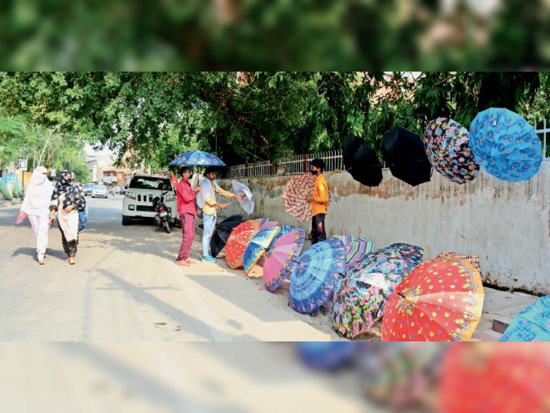 छांव का जुगाड़... छाेटूराम चाैक पर सड़क किनारे छतरियों की खरीदारी करते युवा। - Dainik Bhaskar