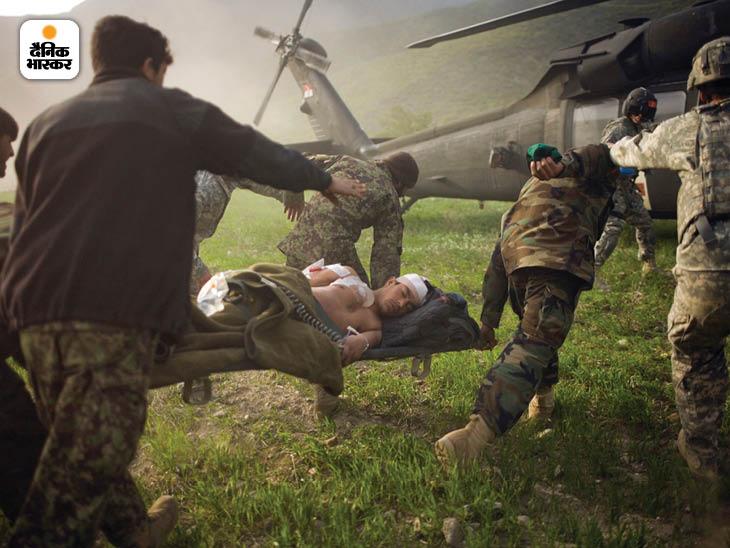 मार्च 2010: अफगानिस्तान के कुनार प्रांत में एक घायल अफगान पुलिस अधिकारी को अमेरिकी हेलिकॉप्टर में ले जाते उसके साथी। फोटो: मोइसेस समन