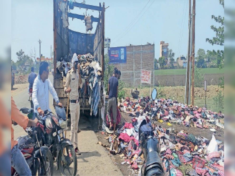 घटना के बाद कई लोग आग से बचे कपड़ों को उठा कर ले जा रहे थे इसलिए ट्रक के पास पुलिस जवान की तैनाती करना पड़ी। - Dainik Bhaskar