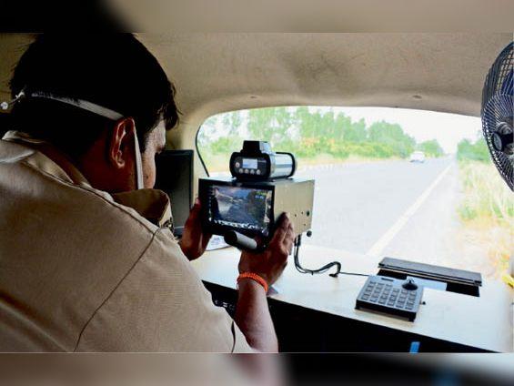 नई इंटरसेप्टर गाड़ी में सुनारियां जेल के पास वाहनों की स्पीड जांच करते पुलिस कर्मी। - Dainik Bhaskar
