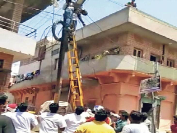पोल पर करंट से बेहोश ठेकाकर्मी को साथी ने ऊपर चढ़ संभाला लोग नीचे तिरपाल थामकर जुट गए, गिरते को थाम बचाई जान जोधपुर,Jodhpur - Dainik Bhaskar