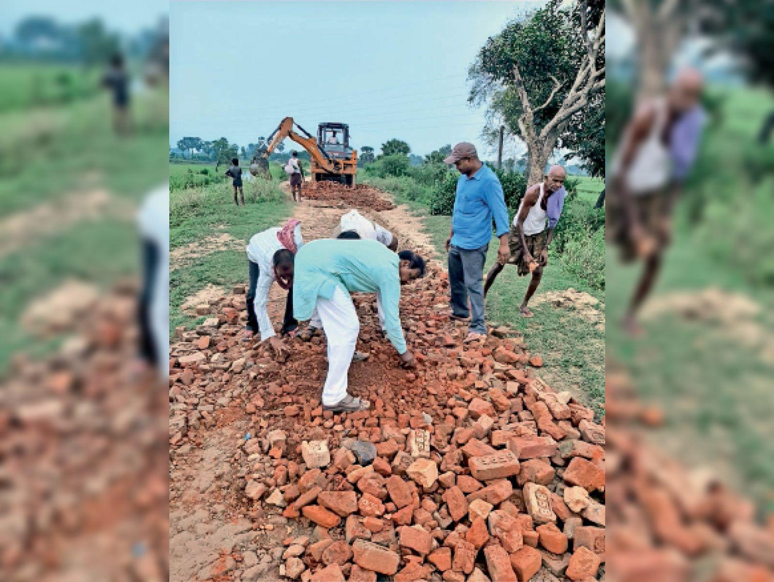 जनप्रतिनिधियों की उदासीनता के बाद श्रमदान कर सड़क बनाते ग्रामीण। - Dainik Bhaskar