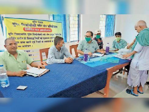 समाधान की जानकारी देते जिला भू -अर्जन पदाधिकारी व सीओ। - Dainik Bhaskar