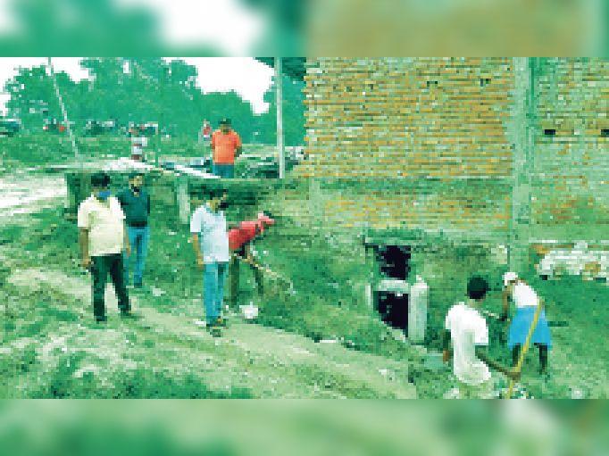 नाले की सफाई का निरीक्षण करते अभियंता व स्वच्छता निरीक्षक। - Dainik Bhaskar