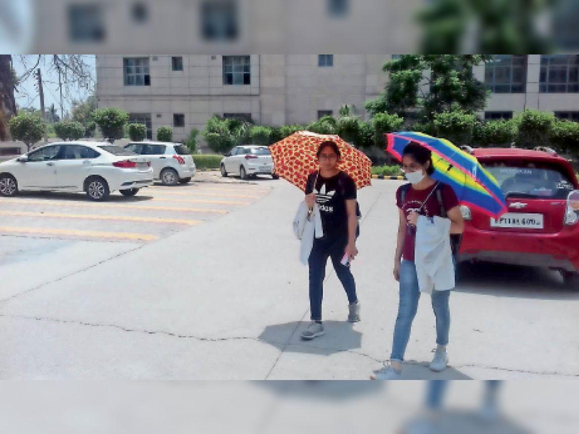 छात्राएं दोपहर को पढ़ाई करने के बाद अपने घर की ओर जाते समय गर्मी से बचने के लिए छतरी का उपयोग करते हुए। फोटो |भास्कर - Dainik Bhaskar