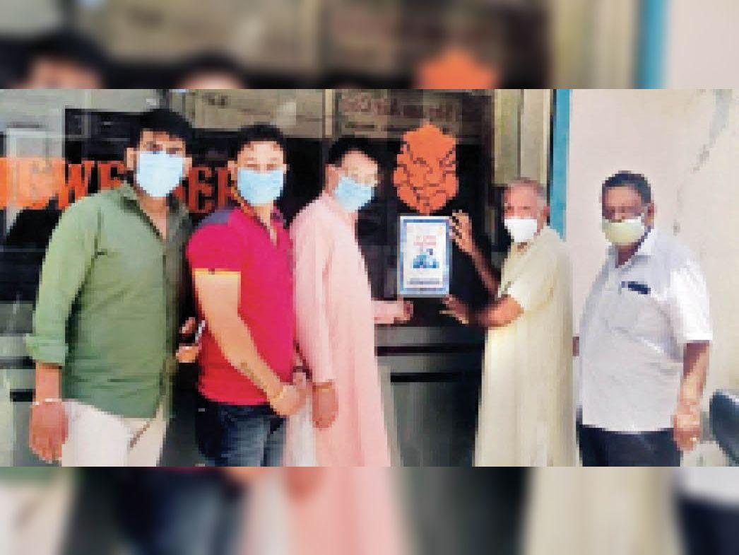 वैक्सीनेशन को लेकर  स्वर्णकार संघ  टीकाकरण के पोस्टर अपनी दुकानों पर लगाते  हुए। - Dainik Bhaskar