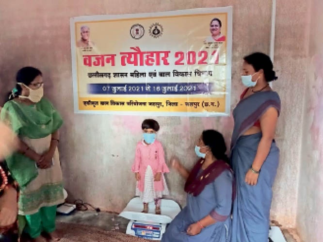 आंगनबाड़ी केंद्र में बच्चे का वजन करते कार्यकर्ता। - Dainik Bhaskar