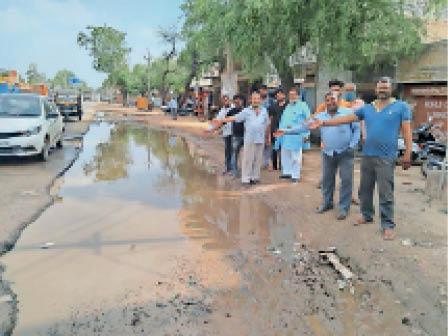 महेंद्रगढ़ रोड के साथ भरे गंदे पानी को दिखाते आसपास के दुकानदार। - Dainik Bhaskar