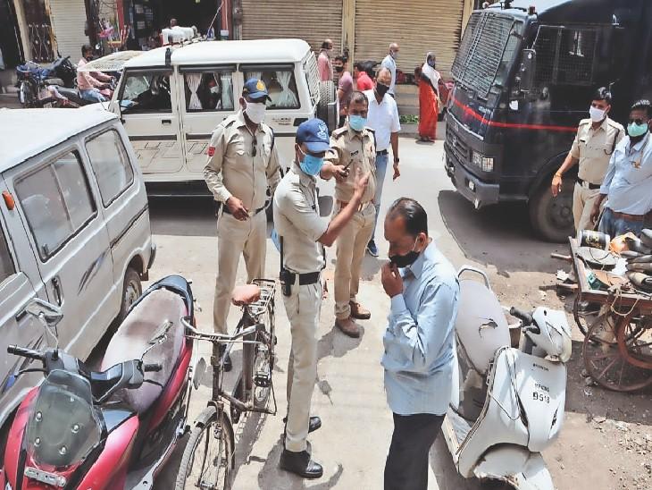 मास्क नहीं पहनने पर चलित जेल में जाने का बोलते पुलिस अधिकारी। - Dainik Bhaskar