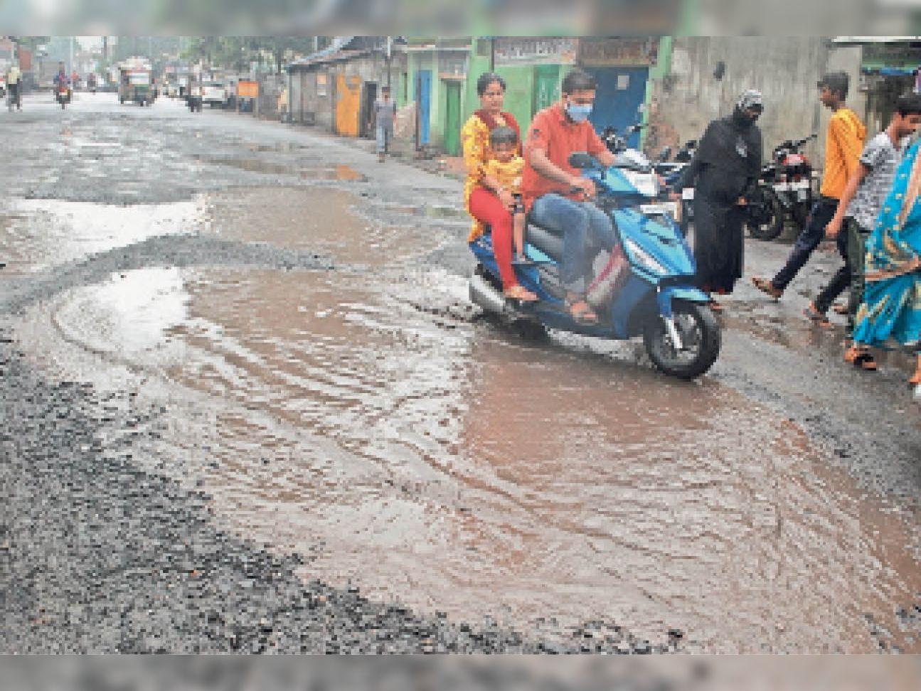 झरिया-सिन्दरी मुख्य मार्ग में सड़क पर बने गड्ढे और जल जमाव। - Dainik Bhaskar