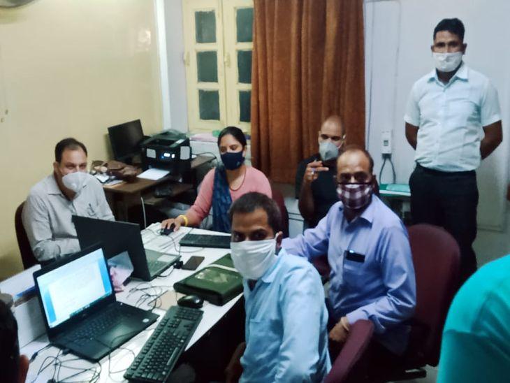 दफ्तर में कार्रवाई करती ACB की टीम और पीछे खड़ा आरोपी राजस्थान लोक सेवा आयोग अजमेर का जूनियर अकाउंटेंट सज्जन सिंह गुर्जर।