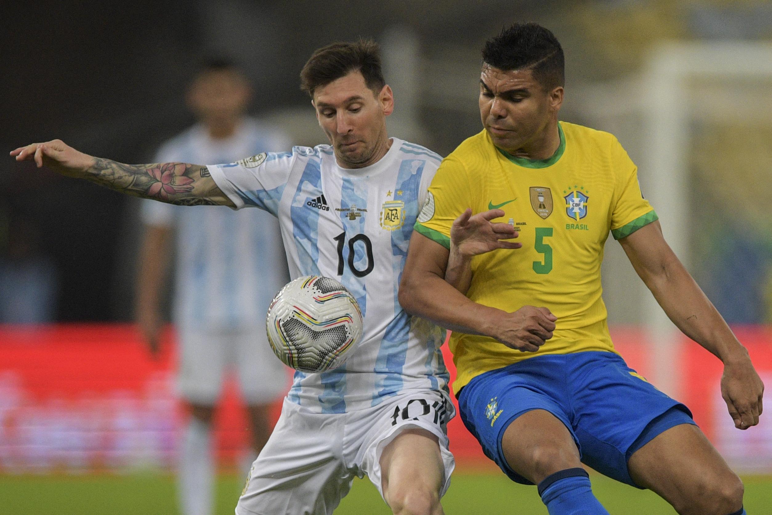 ब्राजील के मिड-फील्डर कैसेमीरो (दाएं) से बॉल हासिल करने की कोशिश करते लियोनल मेसी।