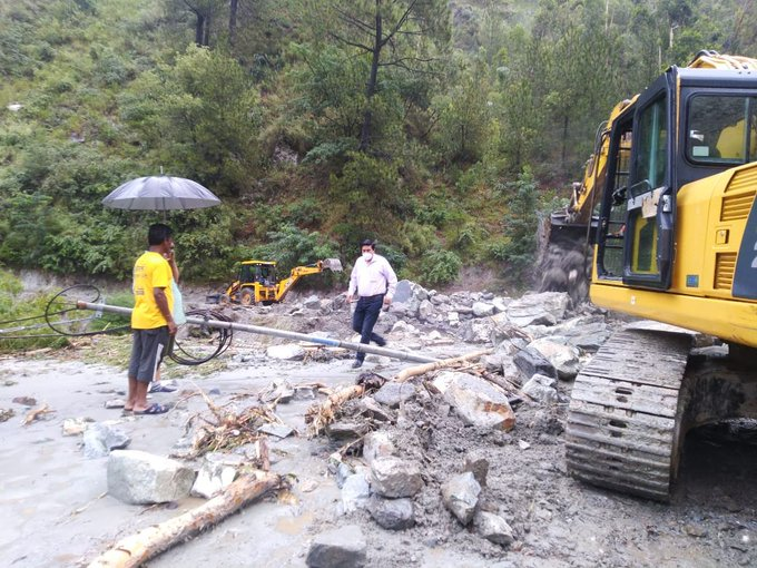 शिमला में बारिश के कारण क्षतिग्रस्त हुई सड़क से मलबा हटाते सरकारी कर्मचारी।