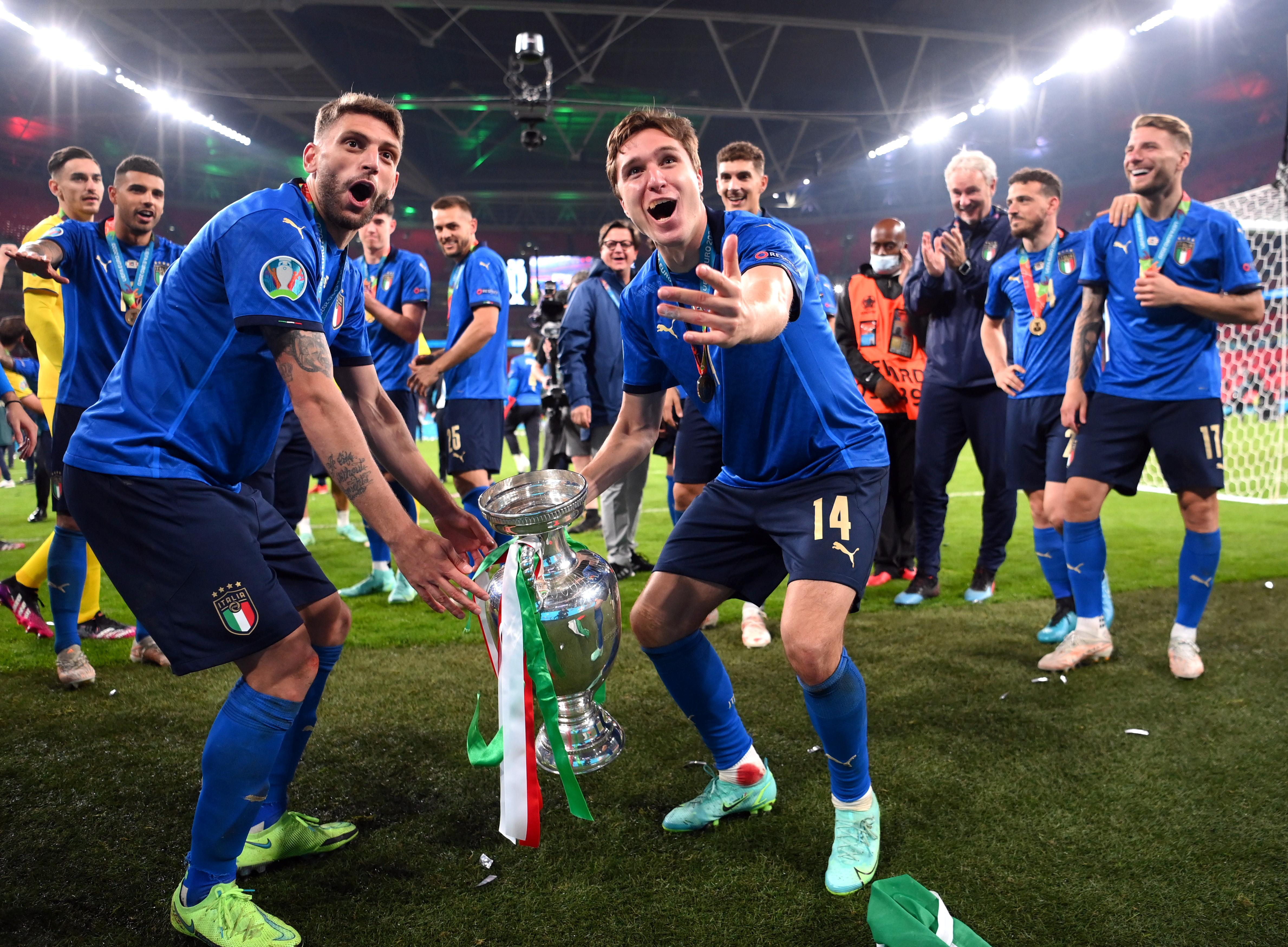 ट्रॉफी के साथ जश्न मनाते इटली के खिलाड़ी।