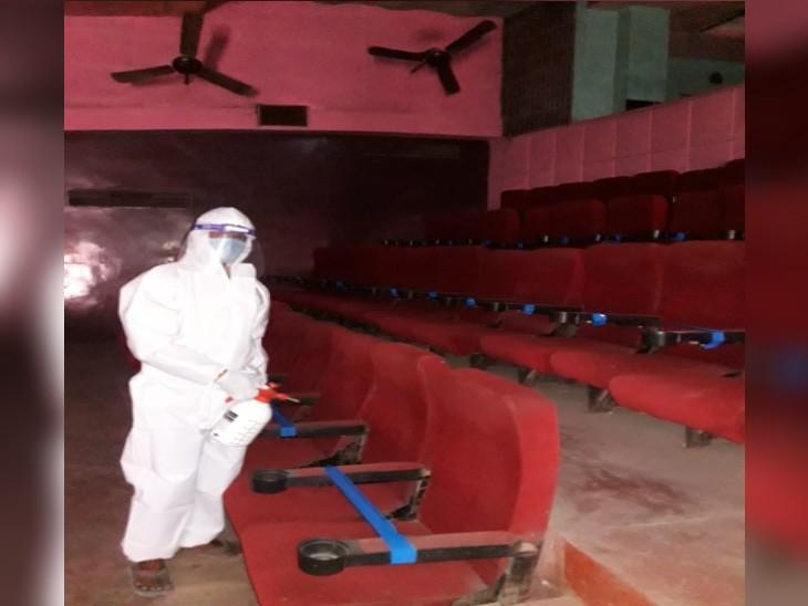 सिनेमा हॉल के अंदर सीट को सैनिटाइज करता कर्मचारी, दो सीट के बीच में एक सीट पर फीता बांधा गया है, जिससे सोशल डिस्टेंस बना रहे