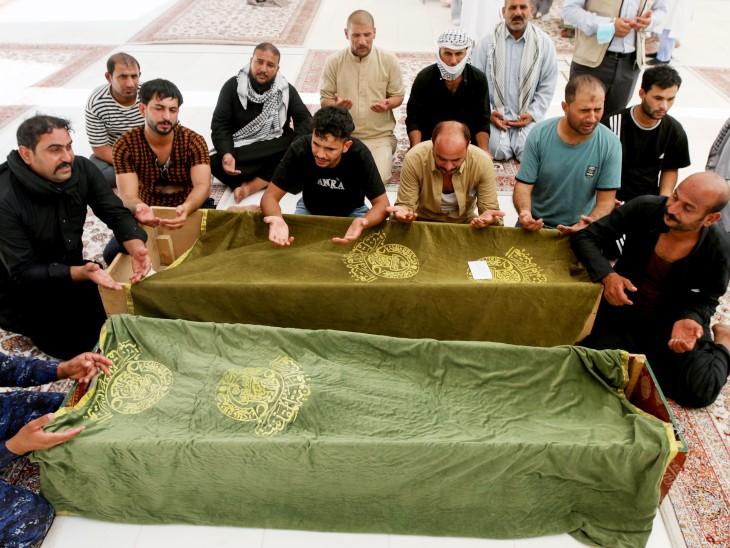 इस हादसे में जान गंवाने वाले लोगों को नजफ में दफनाया गया। फोटो में शवों के पास बैठकर दुआ पढ़ते लोग।