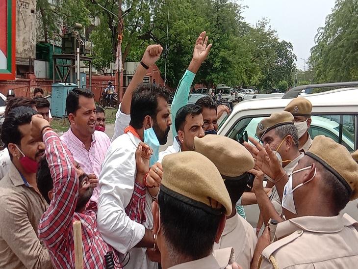कांग्रेस के खिलाफ नारेबाजी करते हुए भाजपा कार्यकर्ताओं को समझाती पुलिस।