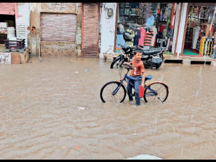 मंडावा. पुराने बैंक ऑफ बड़ौदा के सामने मुख्य सड़क पर भरे हुए बरसात के पानी में साइकिल पर भीगता बच्चा। - Dainik Bhaskar