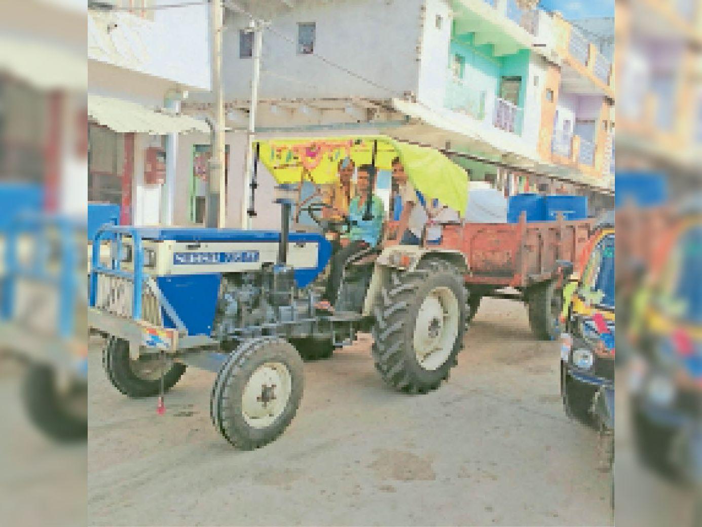 खेतों में लगे ट्यूबवैल से ट्रैक्टर-ट्रॉली में पानी भरकर ला रहे लोग। - Dainik Bhaskar