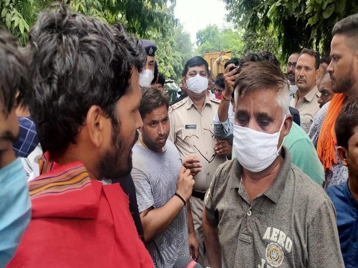सेक्टर 25 बूस्टर पर प्रदर्शनकारियों के बीच में फंसे एक्सईएन मदनलाल शर्मा, सामने लाल रंग के गमछे में खड़े निगम पार्षद जयवीर खटाना