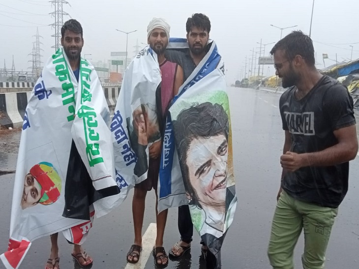 दिल्ली में बारिश होने पर बैनर से बचने का सहारा लेते हुए।