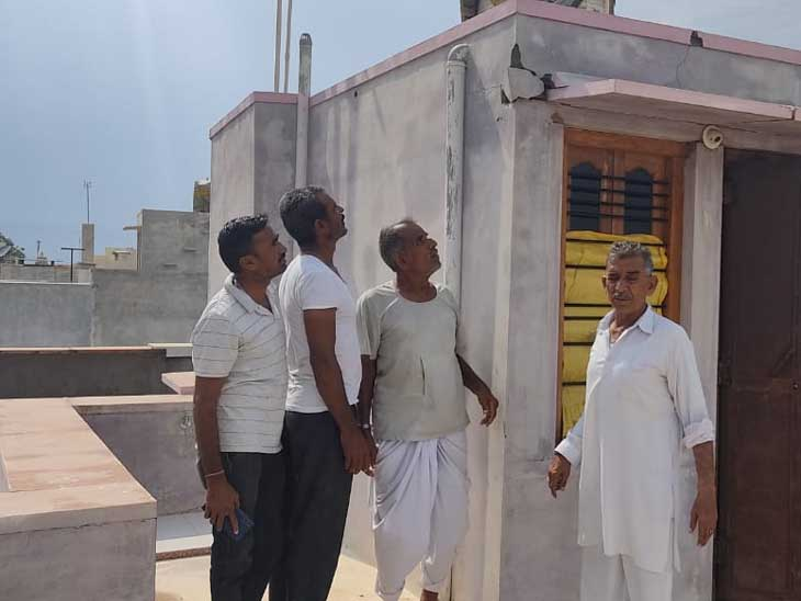 जोधपुर जिले के भावी में मकान पर बिजली गिरने से आई दरार देखते लोग। फोटो- महेंद्र ढाका - Dainik Bhaskar