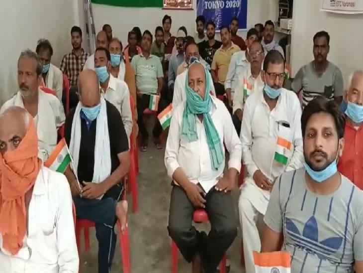 प्रधानमंत्री का संबोधन व बातचीत सुनने के दौरान हाथों में तिरंगा लेकर बैठे दिखे ग्रामीण।