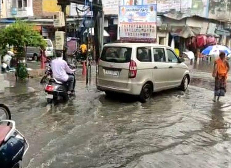 सुमेरपुर के बाजार में सड़कों पर बहता बरसाती पानी से होकर गुजरते वाहन चालक। - Dainik Bhaskar